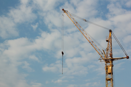 Industrial construction building crane against blue cloudy sky in background