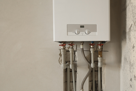 Installation of home gas heating boiler with red taps close up