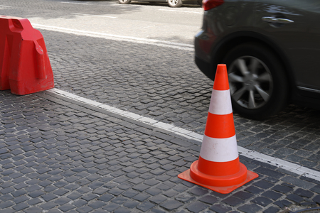 Traffic cone on the cobble stone road with car