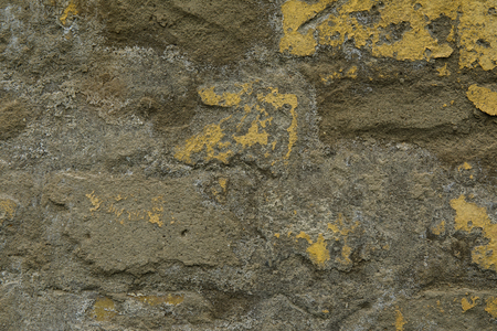 Background of yellow and gray grungy brick wall close up