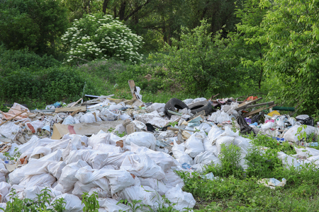 Landscape view on a green forest and grass with huge garbage dump.