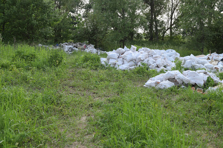 Landscape view on a green forest and grass with huge garbage dump. Reklamní fotografie