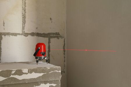 Laser level measuring tool red color in construction site.