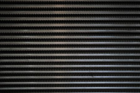 Black surface of a latticed metal fence with jagged stripe elements texture Foto de archivo