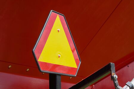Construction warning sign on blur traffic road on red metal background.
