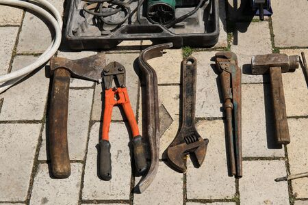 adjustable wrench and other tools on the ground.