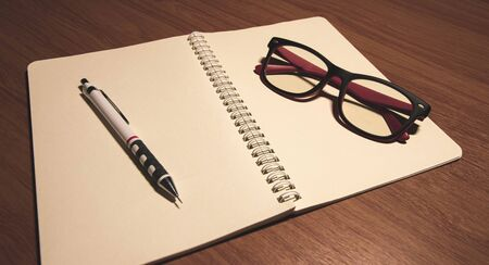 notebook with pen and glasses on wooden table. 스톡 콘텐츠 - 132039574
