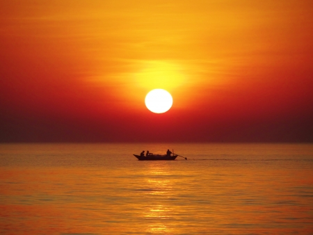 evenings: Sun setting into the sea while a fishing boat sets out for the evenings fishing - Kerala, India