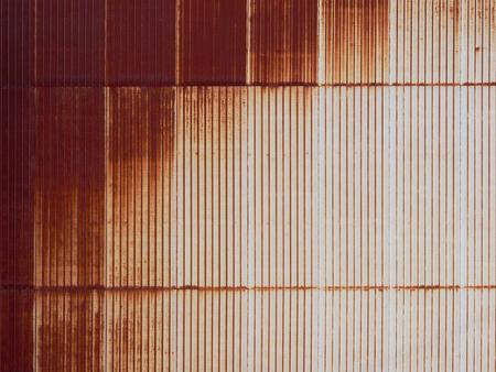 Old oxidized (rusty) zinc sheet wall with strip pattern