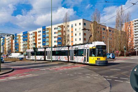 Modern yellow tram crossing the street in Berlin Hellersdorf 写真素材
