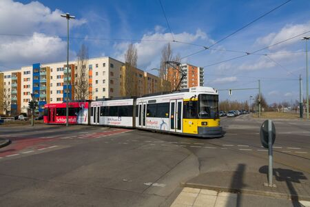 Modern yellow tram crossing the street in Berlin Hellersdorf