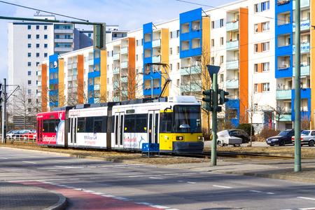 Modern yellow tram crossing the street in Berlin Hellersdorf Editorial