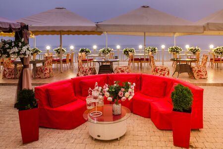 Red couch in a beach bar in the evening