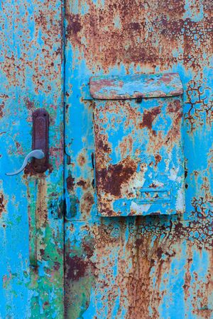 A blue rusty door with a rusty postbox