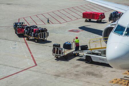 Bagagiste travaillant à l'aéroport. Chargement d'un avion