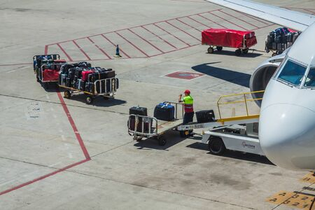 Baggage handler working at the airport. Loading a plane 版權商用圖片