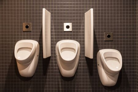 Three urinals in a restroom, two for man, one for boy