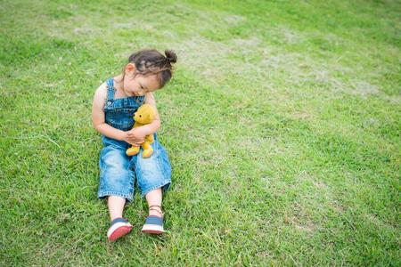 overol: Niña jugando con un oso de peluche con el mono