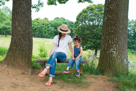 mother on bench: Mother and daughter sitting on a bench Stock Photo