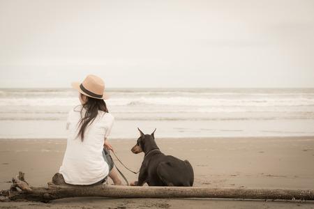 女と海に座っている犬 写真素材