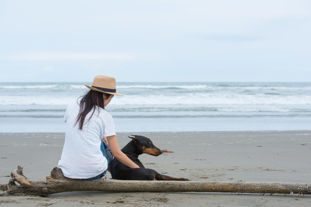 Woman and dog sitting in the sea Imagens