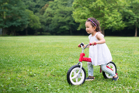 girl riding a red bicycle
