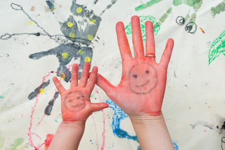 母と子の手が赤く塗られています。