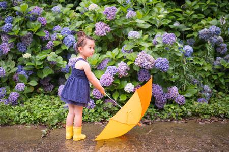 rain boots: Chica con un paraguas en frente de hortensias