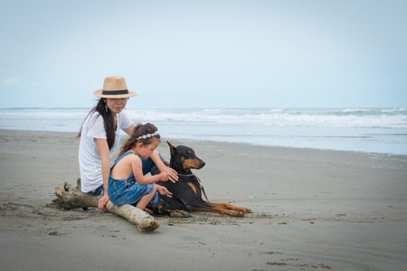 Mother and daughter and  dog sitting on the beach