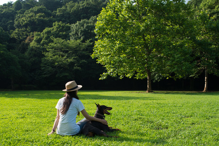 Woman relaxing on the lawn along with the Doberman