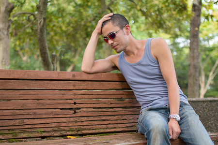sit: Men sit on a bench