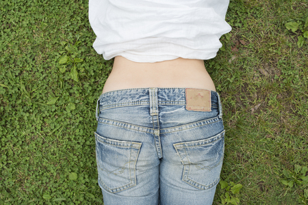 Woman waist and bottom in jeans on the green grass