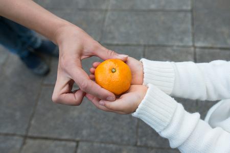 Holding a mandarin orange