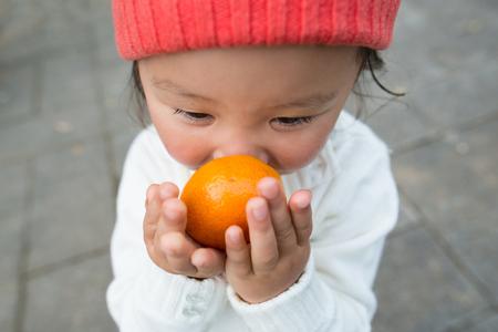 Little girl smelling an orange Stock Photo