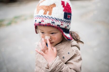 rowdy: Little girl has a bandage on her nose Stock Photo