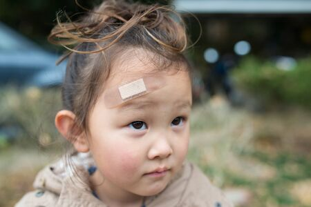 rowdy: Girl putting on the bandage on her forehead