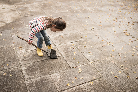 Little girl sweeping up dead leaves