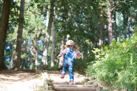overalls: Girl to climb the stairs of the forest Stock Photo