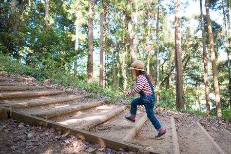 Fille à monter les escaliers de la forêt