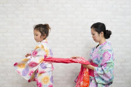 niños vistiendose: Madre ayudar a su hija a vestirse con yukata