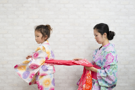 Mother helping her daughter to get dressed in yukata