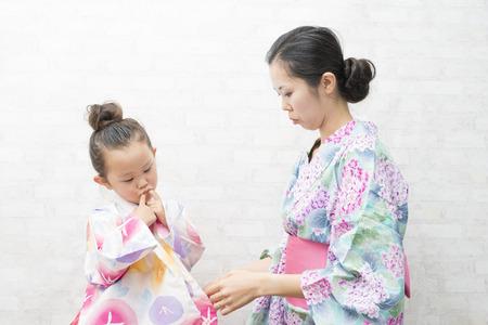 get dressed: Mother helping her daughter to get dressed in yukata