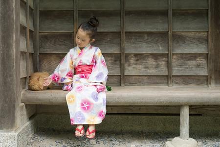Girl stroking a cat wearing a yukata