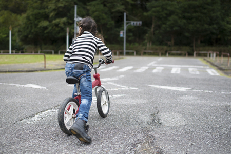 Happy Little Girl Playing on a Bicycle