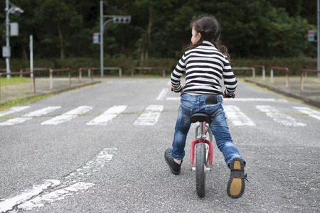 Little girl riding on the bicycle Standard-Bild