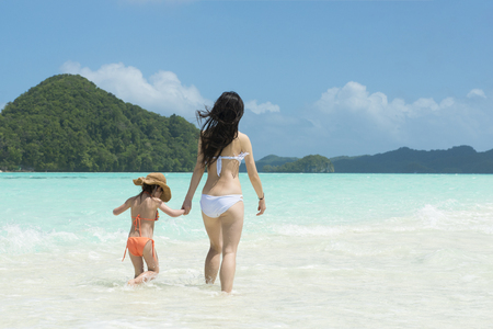 Mother and daughter playing on a beautiful beach
