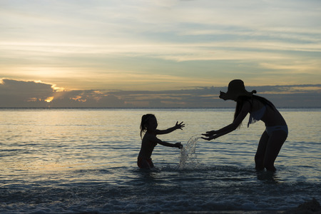 Parent and child silhouette playing in the evening of the beach