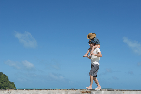 Father and daughter walking to the piggyback on the beach