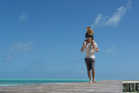 exhilarating: Father and daughter walking to the piggyback on the beach