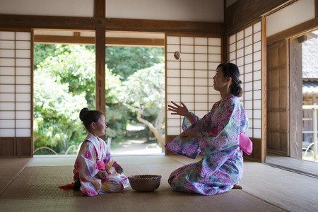 Mother and daughter playing in a Japanese room wearing a Yukata